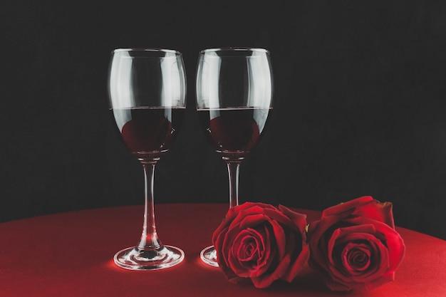 Bottiglia di vino con dos copas y una rosa encima de una mesa