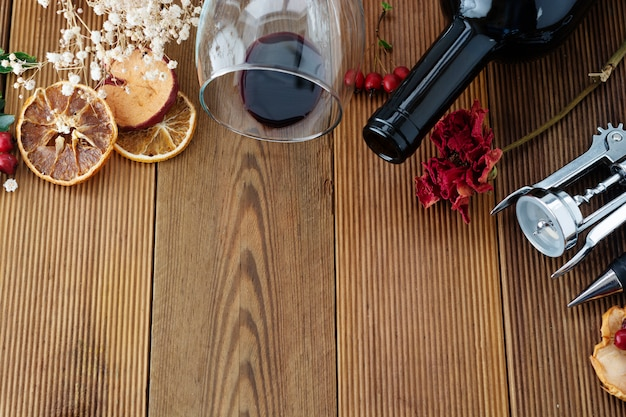 Bottiglia di vino con il bordo di legno rustico della corckscrew del bicchiere di vino, copyspace. disteso.