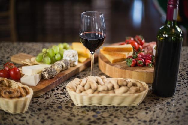 Bottiglia di vino con un bicchiere e un briciolo di cibo