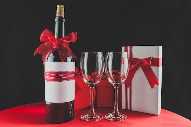Bottiglia di vino con un nastro rosso e due bicchieri vuoti