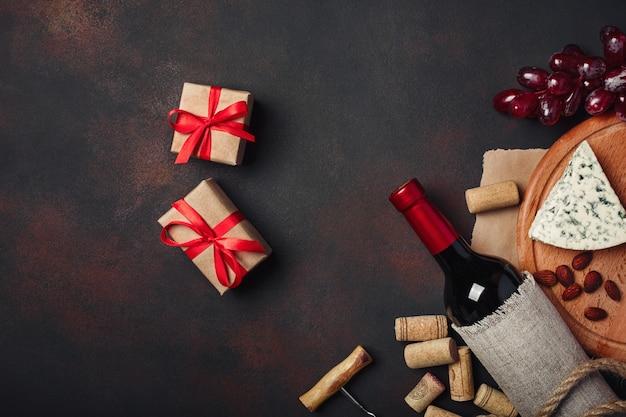Bottiglia di vino, confezione regalo, uva rossa, mandorle, cavatappi e tappi di sughero, vista dall'alto