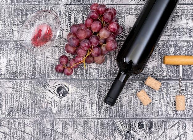 Bottiglia di vino di vista superiore con l'uva sull'orizzontale di legno bianco