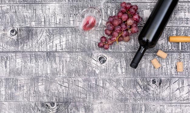 Bottiglia di vino di vista superiore con lo spazio della copia e dell'uva sull'orizzontale di legno bianco