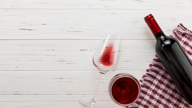 Bottiglia di vino di vista superiore con vetro su fondo di legno