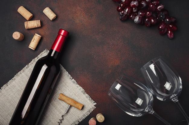 Bottiglia di vino, due bicchieri, cavatappi e tappi di sughero