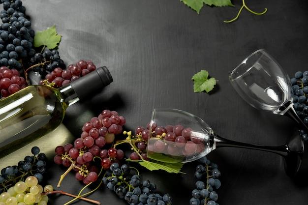 Bottiglia di vino, due bicchieri di vino e uva fresca