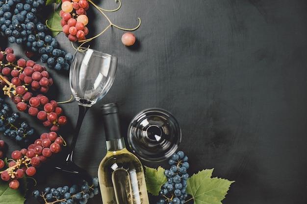 Bottiglia di vino, due bicchieri di vino, uva e foglie fresche