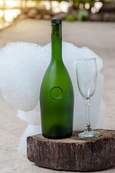 Bottiglia di vino e bicchiere di champagne con sfondo bianco bolle