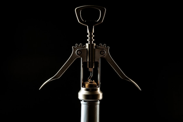 Bottiglia di vino e cavatappi sul buio