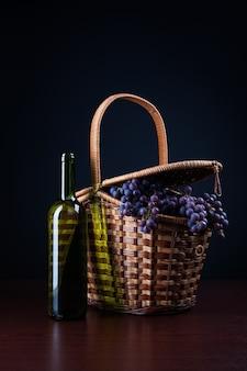 Bottiglia di vino e cestino con uva