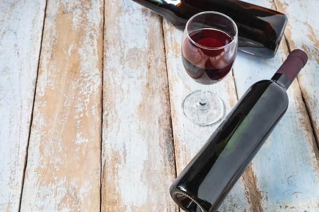 Bottiglia di vino e di vetro di vino su vecchio fondo di legno