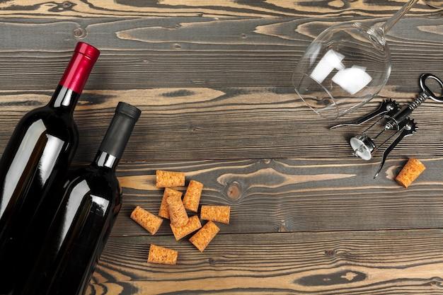 Bottiglia di vino e sughero e cavatappi sulla tavola di legno