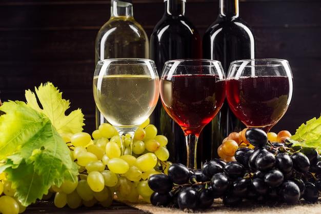 Bottiglia di vino e uva sul tavolo di legno