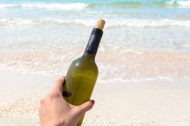 Bottiglia di vino in sabbia sulla spiaggia