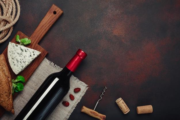 Bottiglia di vino, mandorle, cavaturaccioli e tappi di sughero, sulla vista superiore del fondo arrugginito