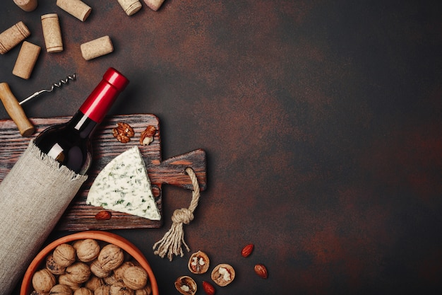Bottiglia di vino, noci, formaggio blu, mandorle, cavatappi e tappi di sughero, su fondo arrugginito vista dall'alto
