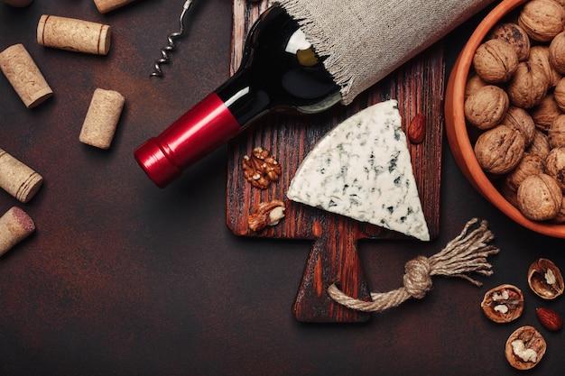 Bottiglia di vino, noci, formaggio blu, mandorle, cavatappi e tappi. vista dall'alto