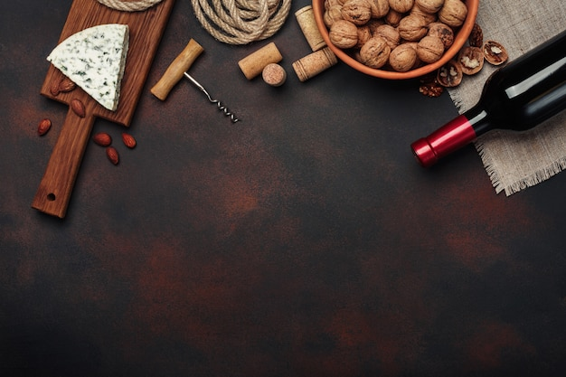 Bottiglia di vino, noci, mandorle, cavatappi e tappi di sughero, su fondo arrugginito vista dall'alto