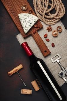 Bottiglia di vino, noci, mandorle, cavatappi e tappi di sughero, vista dall'alto