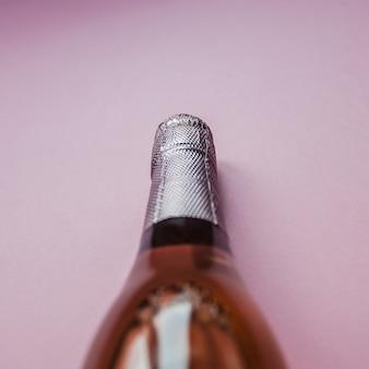 Bottiglia di vino rosa champagne su sfondo rosa
