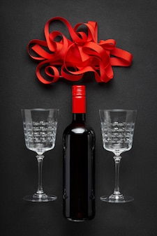 Bottiglia di vino rosso, bellissimi bicchieri per vino e un nastro rosso.