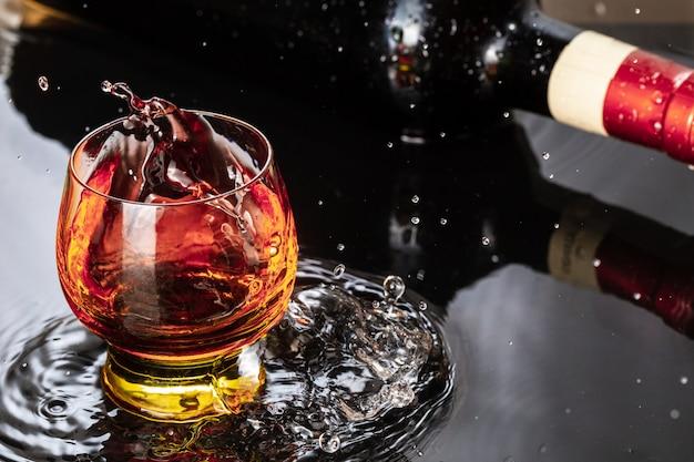 Bottiglia di vino rosso con bicchiere di vino. spruzzi d'acqua e gocciolina sul riflesso nero.