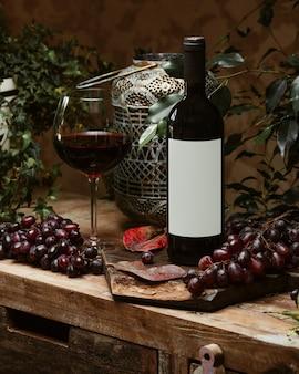 Bottiglia di vino rosso e un bicchiere di vino rosso in stile rustico