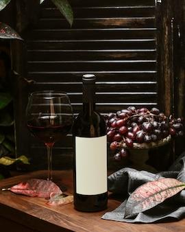 Bottiglia di vino rosso e un bicchiere di vino rosso
