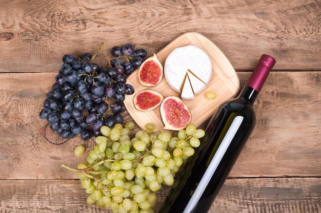 Bottiglia di vino rosso, uva, formaggio camambert e fichi sul vecchio tavolo di legno rustico