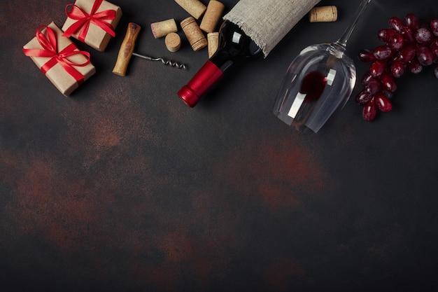 Bottiglia di vino, scatola regalo, uva rossa, cavatappi e tappi di sughero,