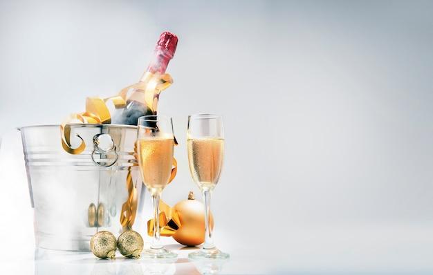 Bottiglia di vino sul secchiello del ghiaccio e un paio di occhiali con decorazioni natalizie