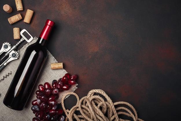 Bottiglia di vino, uva rossa, cavatappi e tappi di sughero, vista dall'alto