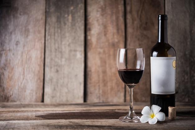 Bottiglia di vino, vetro e fiore bianco su fondo di legno
