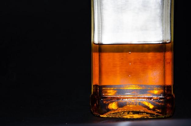 Bottiglia di whisky mezzo piena. imbottiglia la mano di un uomo. whisky single malt. alcol. una bottiglia di whisky da diverse angolazioni. fondo della bottiglia, collo con tappo. dipendenza da alcol