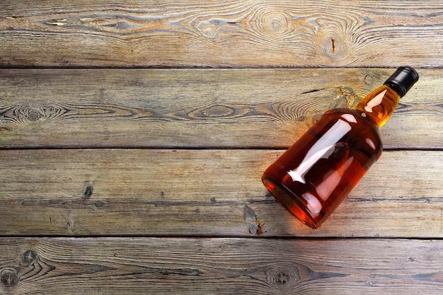 Bottiglia di whisky sulla disposizione piana del fondo di legno scuro