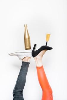 Bottiglia e bicchiere di bevanda su suole di scarpe su gambe di donna e uomo