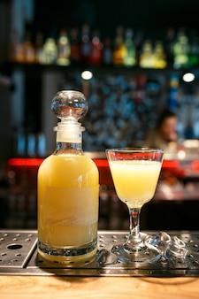 Bottiglia e bicchiere pieno di bevanda alcolica gialla sul bancone del bar