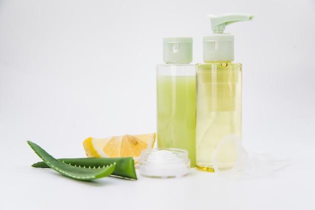 Bottiglia e crema dello spruzzo naturale del limone e dell'aloe vera per bellezza su fondo bianco