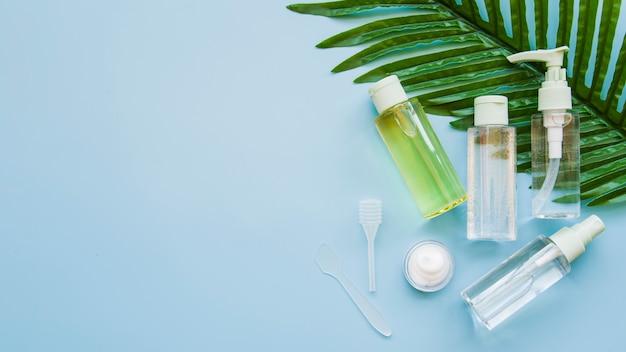 Bottiglia e crema trasparenti del contenitore dei cosmetici con foglia fresca verde contro fondo blu