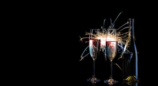 Bottiglia e due bicchieri di champagne in luce multicolore del bengala