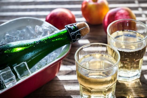 Bottiglia e due bicchieri di sidro su legno