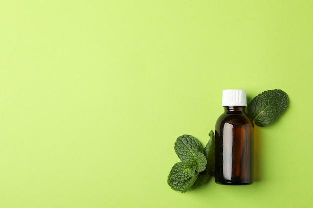 Bottiglia e menta mediche su verde, spazio per testo