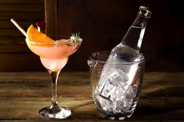 Bottiglia e un bicchiere di alcol cocktail con ghiaccio e arancia su uno sfondo di legno scuro