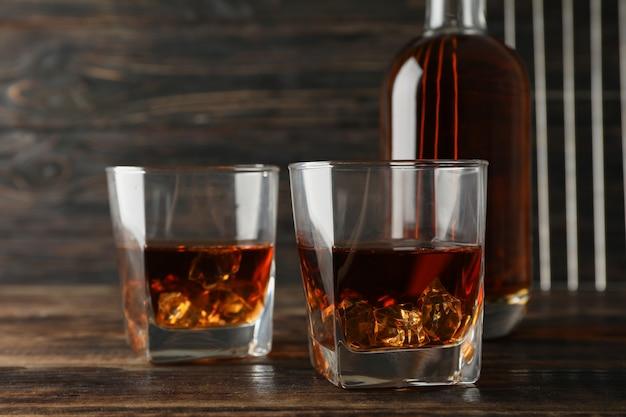 Bottiglia e vetri di whiskey su fondo di legno, spazio per testo