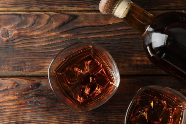 Bottiglia e vetri di whiskey su fondo di legno, vista superiore