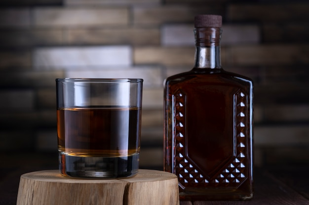 Bottiglia e vetro con alcool su un supporto di legno contro un muro di mattoni