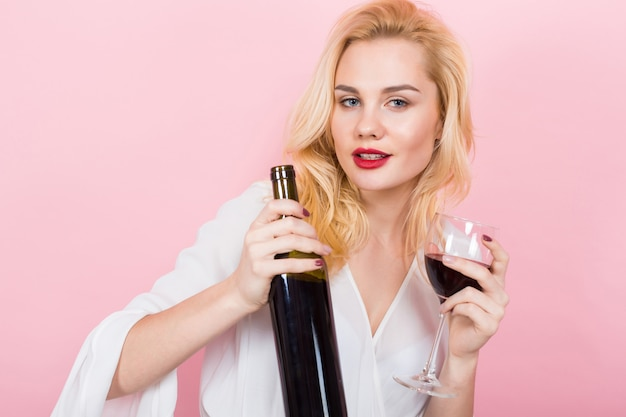 Bottiglia e vetro di vino biondi della holding della donna