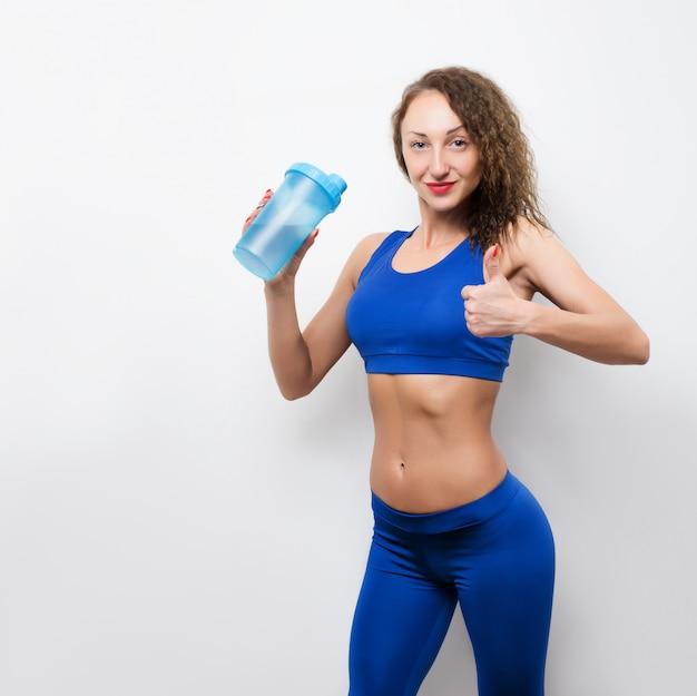 Bottiglia felice della tenuta della donna di forma fisica sopra la scena bianca. guardando la fotocamera, pollice in su.