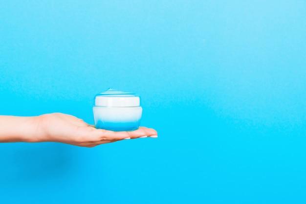 Bottiglia femminile della crema della tenuta della mano di lozione isolata. la ragazza dà a barattolo i prodotti cosmetici sull'azzurro
