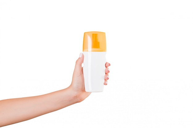 Bottiglia femminile della crema della tenuta della mano di lozione isolata. la ragazza dà prodotti cosmetici